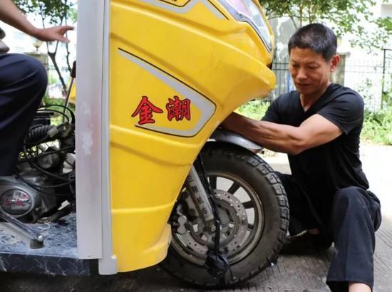 图为:陈吉川在修车。罗浩榕 摄
