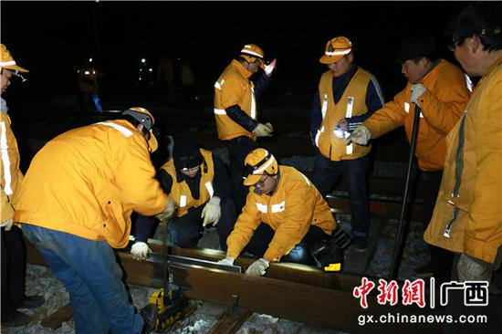 工长梁明在与焊修工人们进行对轨作业。冷鹏飞 摄