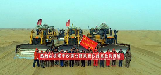 """筑路工人在""""第一师十四团——塔里木沙漠公路""""终点留影。"""