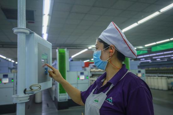 2019年3月2日,工人在新疆呼图壁县五工台镇奥美医疗生产车间工作。(陶维明 摄)