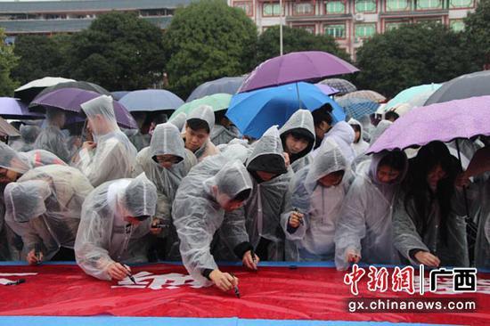 学生雨中坚持拒毒签名。陶云 摄