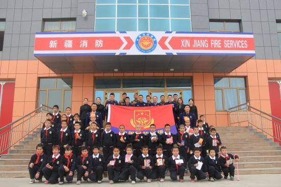 图为库车县消防大队消防指战员与儿童福利院孤儿合影留念。