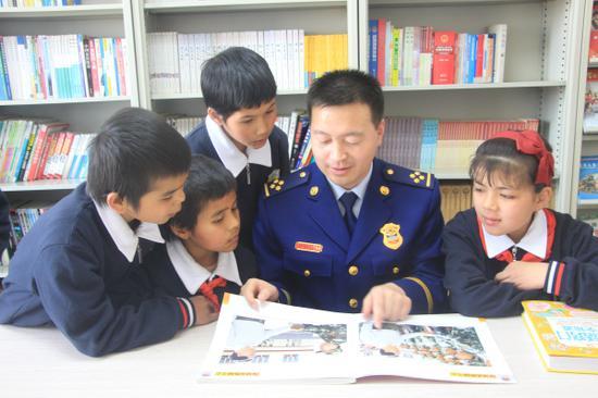 图为消防指战员辅导儿童福利院孤儿学习。
