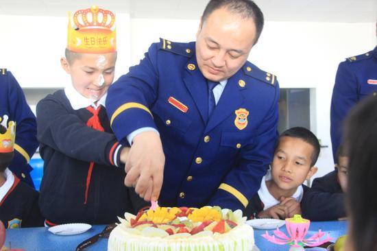 图为消防指战员为儿童福利院孤儿过生日。