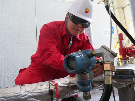 采气一厂技术人员采集气田生产现场仪表参数。(拍摄:蔺媛)