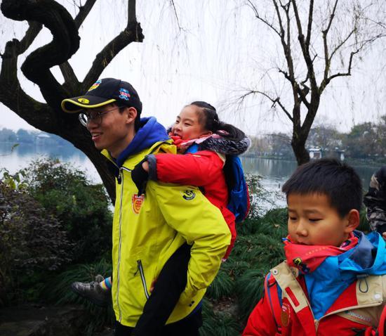 活动中领队对孩子无微不至的照顾。  于志鹏 摄