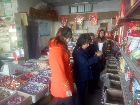 执法人员在检查商店商品情况