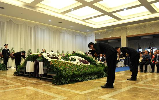 """图为:四名礼宾工作人员在对""""逝者""""(鲜花代替)鞠躬致礼。   张茵 摄"""