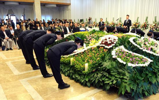 """图为:工作人员在向""""逝者""""(鲜花代替)鞠躬道别。   张茵 摄"""