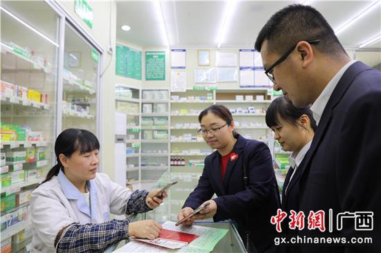 邮储银行贺州市分行开展邮爱公益宣传活动 ,药店工作人员在扫码捐赠。