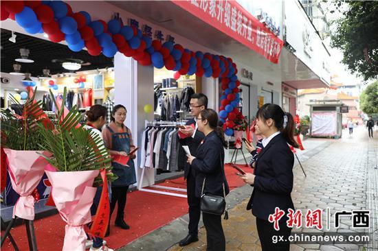 邮储银行贺州市分行员工在向店铺工作人员介绍邮爱公益活动。