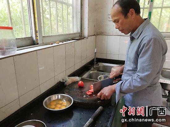 图为李均卓利用下课时间为学生们做午餐。