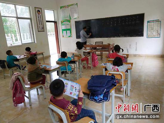 图为李均卓教孩子们拼音。