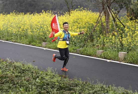 圖為:參加者在跑過油菜花田。  王剛 攝
