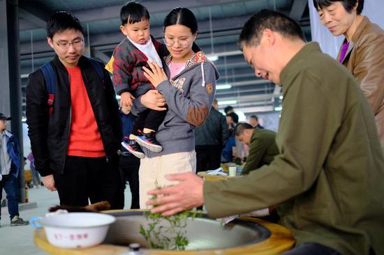 圖為:多位市民在觀看炒茶。  張洋 攝