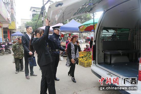 图为干警将被执行人带上警车。法院供图