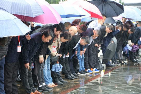 風雨中,海外華僑、烈士家屬莊嚴肅立向革命烈士鞠躬默哀。  文成宣傳部供圖