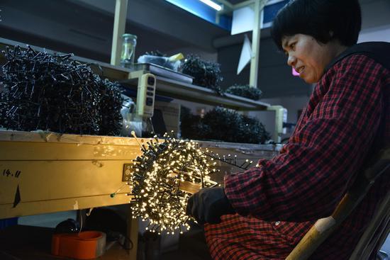 圖為:一位工人正在檢驗彩燈樣品  范宇斌 攝