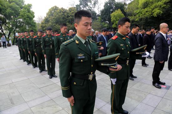 武警官兵們向烈士脫帽致敬。   溫州武警供圖