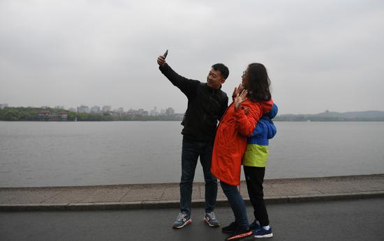 图为:三位游客穿厚衣服在西湖边拍照。王刚 摄