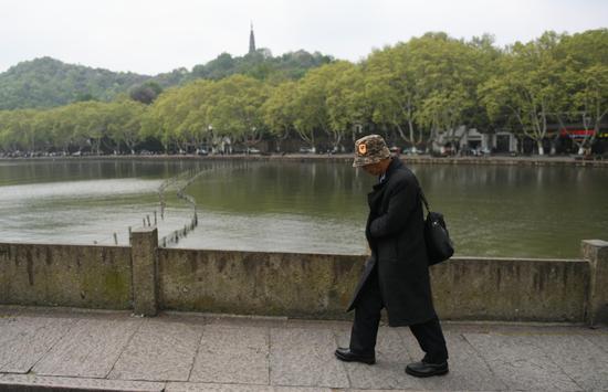 图为:一位游客穿冬装游西湖。王刚 摄