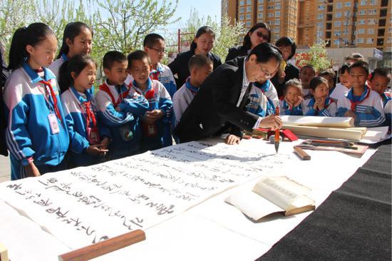 潘蔚林现场为学生们书写书法作品。