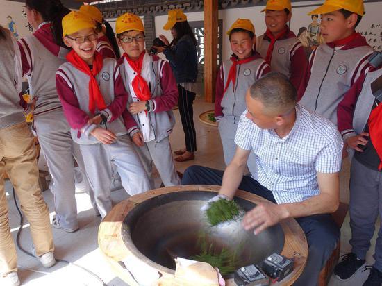學生學習炒茶過程。  錢晨菲 攝