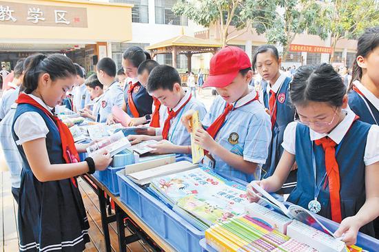 图为学生在世界图书日精品图书展览上阅读书籍。