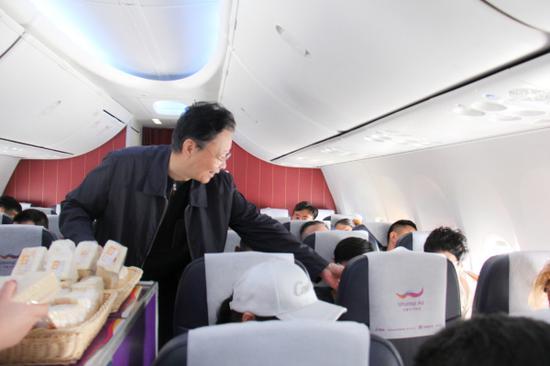 图为乌鲁木齐航空副董事长杨建平为乘客服务。