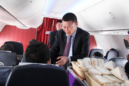 乌鲁木齐航空总裁吴浩与乘务员一起推出餐车为旅客提供餐饮服务。