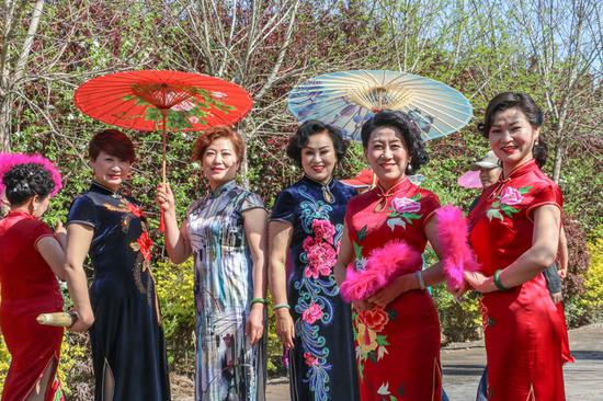 2019年4月28日,在新疆呼图壁县第四届海棠花季乡村文化旅游节活动现场,旗袍秀表演吸引了不少游客驻足欣赏拍照。(陶维明 摄)