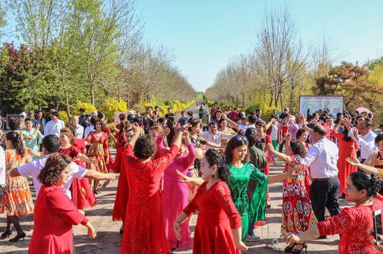 2019年4月28日,在新疆呼图壁县第四届海棠花季乡村文化旅游节活动现场,演员和游客共跳麦西来甫。(陶维明 摄)