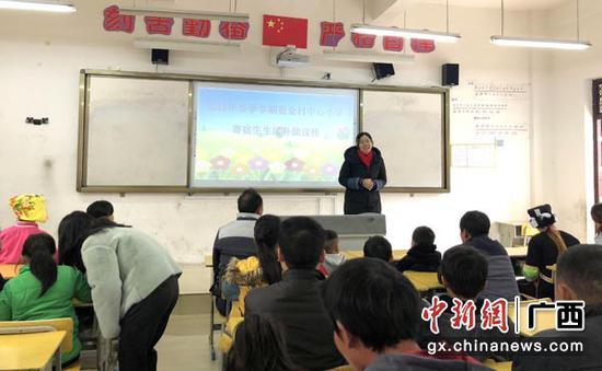 图为家长会上,校长给家长宣传惠民政策。