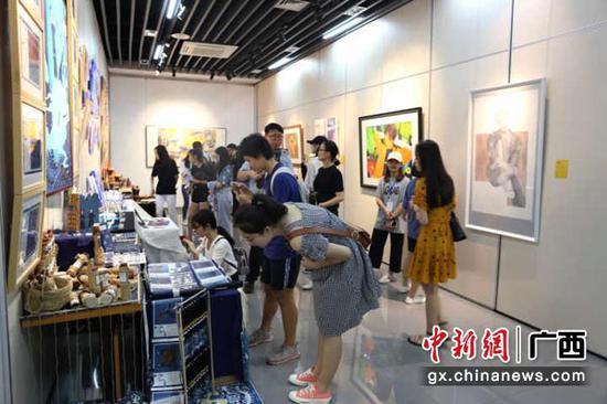 图为学生观看艺术展览。