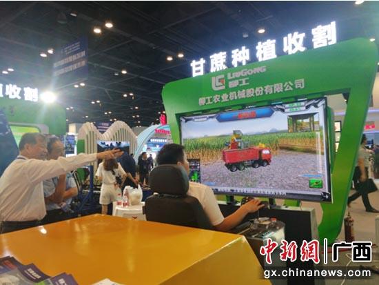 图为参展代表操作感受模拟甘蔗种植收割新技术。 黄译锐 摄