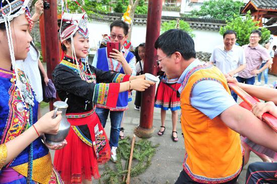 图为:一名华文媒体记者在体验畲族敬酒。  张茵 摄