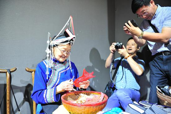 图为:两名华文媒体记者在拍摄畲族老人剪纸。  张茵 摄