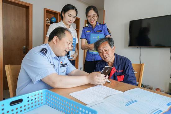 5月30日,便民服务中心、派出所和综合执法局的工作人员上门为外?#27425;?#24037;人员登记办理电子居住证   吴拯 摄