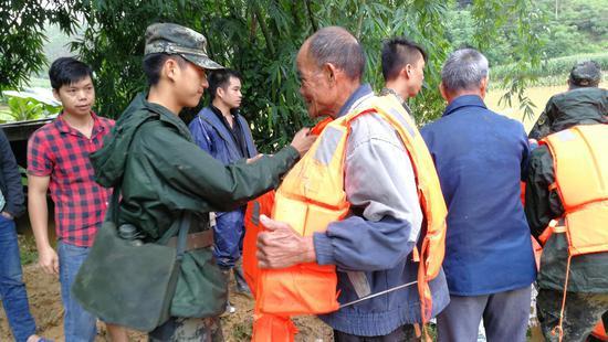 圖為武警官兵正在為老人穿上救生衣。