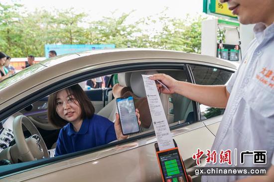 图为车主与工作人员一同展示无感加油扣款单。陈冠言  摄