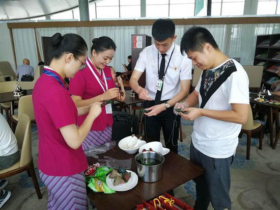 南航地服工作人员和候机旅客一起包粽子。尹丽腊 摄