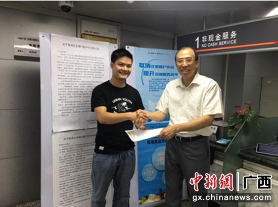 圖為工行廣西分行陳志彪副行長到網點了解新政實施后的企業開戶情況,與企業客戶親切握手。