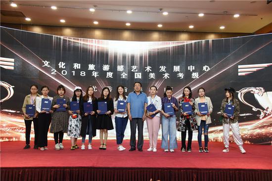 """新疆美术行业名家为获得""""2018全国美术考级优秀辅导教师""""荣誉称号的老师颁发荣誉证书。"""