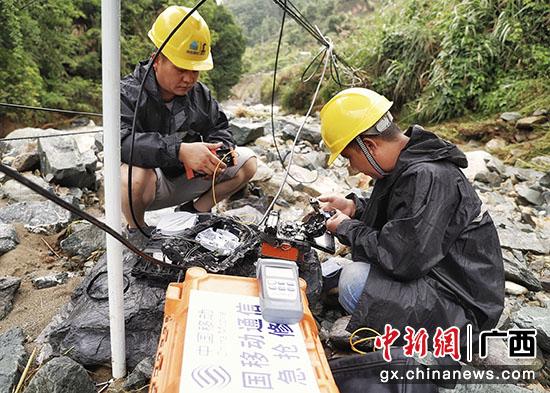 图为通信抢修人员正在被洪水冲刷过的河道进行光缆抢修。
