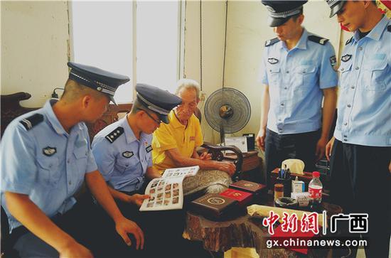 """图为""""兵爸爸""""张德权老人正在向民警介绍参加抗战的战友名册。"""