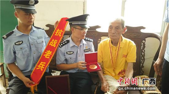 """图为张德权老人正在向民警展示获赠的""""中国人民抗日战争胜利70周年纪念章。"""