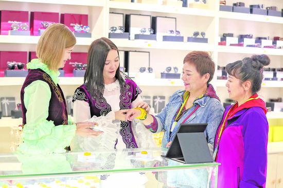 6月12日,哈萨克斯坦姐妹高孜雅(左一)、丽娜(左二)在中哈霍尔果斯国际边境合作中心向中国旅客介绍哈萨克斯坦特色首饰。 □新华社发 周旭摄