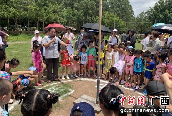 广西骆越文化研究会会长向小朋友讲解日照无影的特别现象。