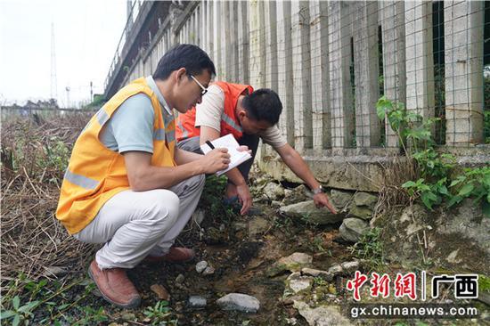 圖為鐵路職工正在記錄水害沖空柵欄設備情況。