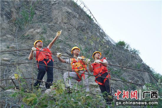 圖為鐵路職工正在危石被動防護網上開展檢查工作。